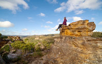 A bushwalker sits high atop a landscape of pagodas, valleys, gullies and canyons