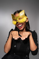 Portrait of attractive young Asian woman in gold cat carnival mask