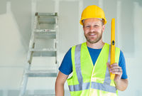 Caucasian Male Contractor With Hard Hat, Level and Safety Vest At Construction Site
