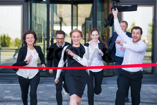 Business people crossing the finish line