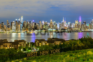 West New York City midtown Manhattan skyline view from Boulevard East Old Glory Park over Hudson River at dusk.