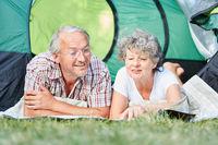 Senioren Paar liegt entspannt im Zelt