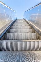 Metallic escalator outside with blue sky