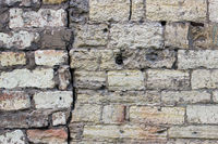 The old wall of beige curves of bricks with a large crack historical stones calcareous tuff. Gatchina, Russia