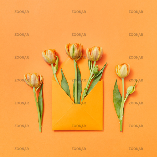 Fresh tulips in a handmade envelope on a yellow background.