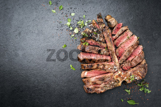 Barbecue dry aged wagyu porterhouse steak sliced and decorated with spice and herbs as top view on a black slate slab with copy space left