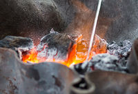 orange glowing coal covered with ash close up in an iron forge