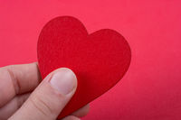 Red color heart shaped object in hand