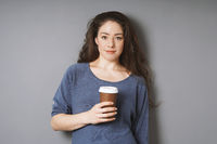 relaxed young woman holding coffee to go in disposable cup