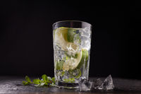 Cocktail with fresh fruit lime, mint and ice in a glass on dark