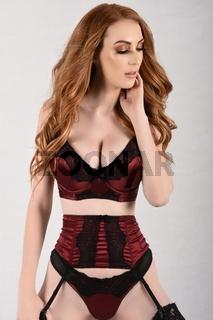 Sexy, grosser, schlanker, vollbusige Rothaarige in sexy roter Unterwasche gekleidet
