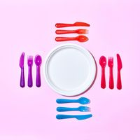 Multicolored plastic utensil around white plate on a light pink.