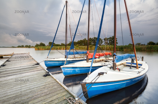 blue yachts by pier on big lake