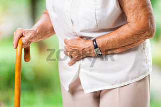 Elderly woman in the 80s with a walking stick and stomach pain
