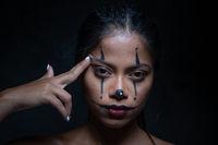 Halloween clown woman portrait making a suicide gesture