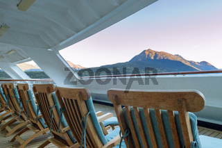 Row of open cushioned wood deck lounge chairs at sunrise in the early morning on outdoor verandah at stern of cruise ship, Skagway, Alaska, USA.