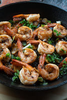 Prawns shrimps roasted on pan with herbs on rustic wooden kitchen table