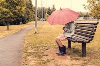 Girl with umbrella sitting on bench