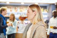 Junge Frau trinkt mit Genuss ein Glas Bier im Pub