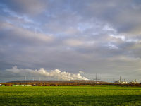 Wind turbines on a heap, steam clouds of a power plant.