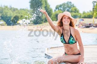 Junge Frau auf einem Steg plantscht mit Wasser