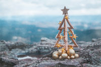 Christmas tree with gold lights and mountain backdrop