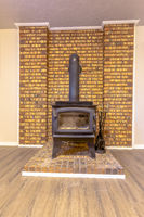 Fireplace inside the room of a home with wood floor and stone brick accent wall