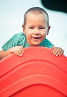 Little smiling boy on a slide