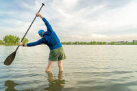 stand up paddler is stretching