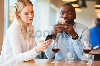 Junges Paar schaut ständig auf Smartphones