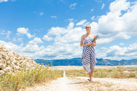 Caucasian young woman in summer dress holding bouquet of lavender flowers while walking outdoor through dry rocky Mediterranean Croatian coast lanscape on Pag island in summertime