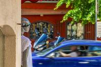 Street corner, mannequin, moving car, motion blur.