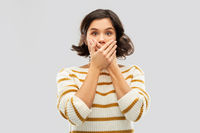 shocked young woman covering her mouth by hands