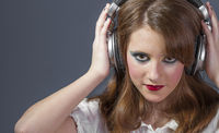 redhead girl with helmet on her head listening to music on a flat gray background
