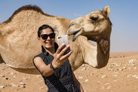 Woman taking selfie with a camel