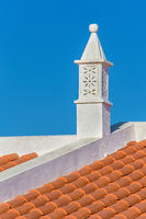 Elegant white chimney on orange roof