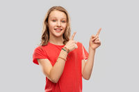smiling teenage girl pointing fingers to something