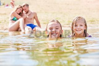 Geschwister schwimmen zusammen im Meer