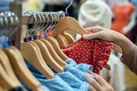 A women is choosing new clothes, shopping in fashion mall, close up of hands