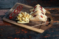 Sandwiches with Turkish sausage (sucuk) and cheese served aise with french fries on rustic wooden table