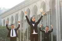 Muslim businesswoman holding a trophy