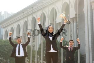 Muslim businesswoman holding a trophy