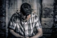 young man thinking against a rustic door background