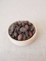 Roasted cocoa beans in a wooden bowl