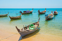 Traditional wooden boats moored at sand beach