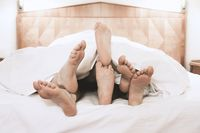 three pairs of feet lying together under bed cover