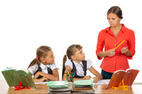 Children at their desks look at the angry teacher with fear