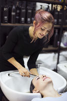 Gorgeous cheerful young woman enjoying head massage while getting her hair washed by a professional hairdresser