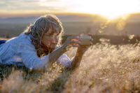Woman taking (selfie) pictures with the smartphone in sunset