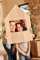 Glückliche Eltern und Kind mit Haus aus Pappe